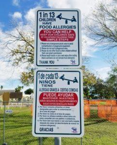 An bilingual allergy awareness park sign.