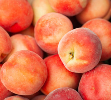 Picked peaches piled into a crate