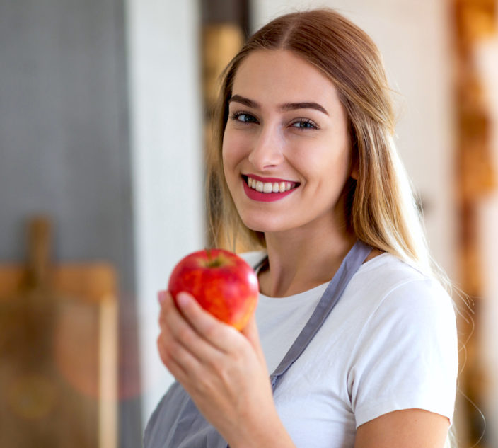 Young woman holding an apple and smiling