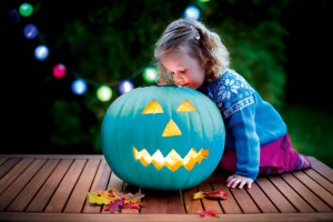 Little girl carving pumpkin at Halloween