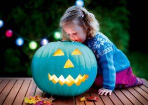 Little girl carving pumpkin at Halloween