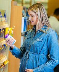 Pregnant woman reading label on prenatal vitamin bottle in pharmacy