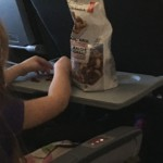 Girl eating trail mix containing nuts on flight