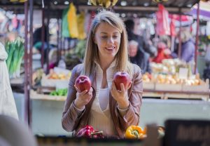 A woman looking at fruit - something to consider with oral allergy syndrome.