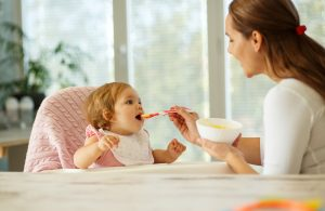 Introducing potentially allergenic foods to a child.