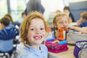 Smiling girl sitting in a school cafeteria.