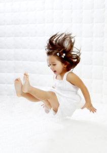 A happy young girl in white dress having fun jumping on mattress.