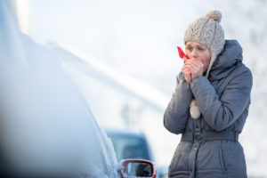 A woman standing outside of her car in the winter. If an epipen is left in the cold, will it be ruined?