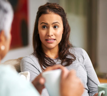 A woman discussing food allergies with a family member.