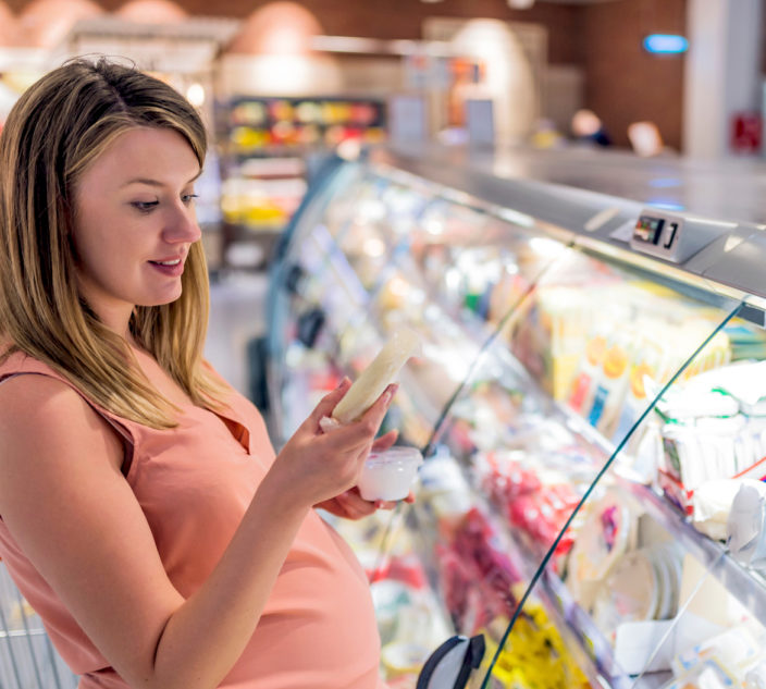 Pregnant mother decides what food to purchase at a grocery store.