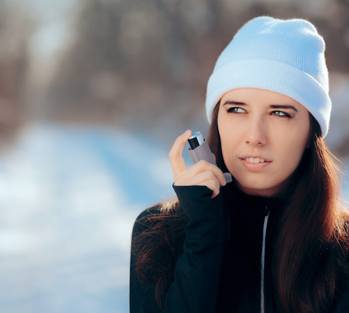 Asthmatic woman managing condition with medication in cold season.