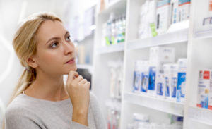 Young woman looking at medications for sale at the drugstore thoughtfully.