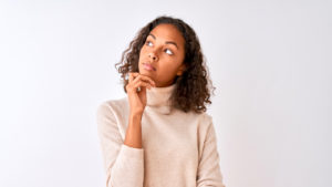 Young woman with hand on chin thinking about question, pensive expression.