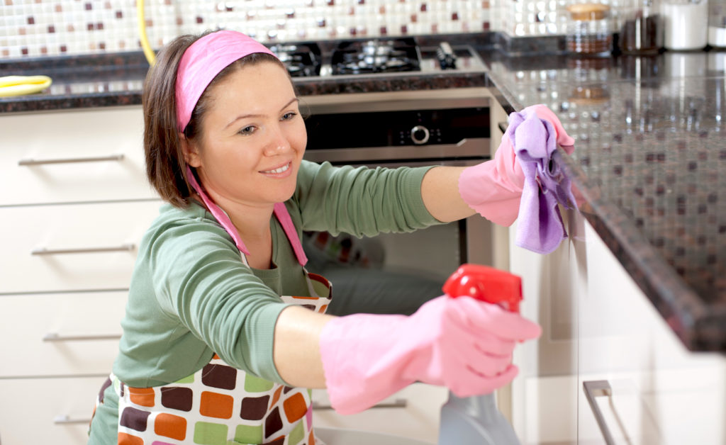 Happy woman is cleaning her home.