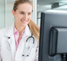 Doctor looking at computer monitor, speaking with patients.