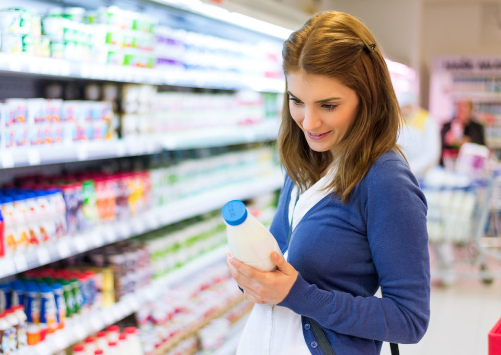 Young woman checking milk's labeling in supermarket.