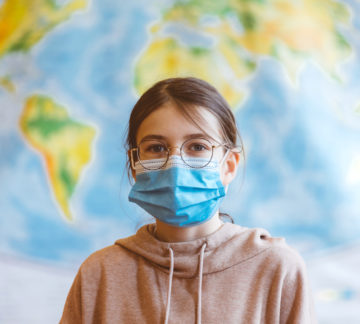 A 11-year-old teenager wearing a N95 Face masks is standing in front of a world map