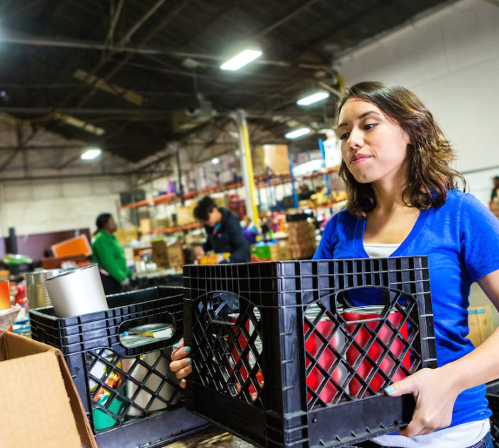 Young woman volunteering to organize donations in large food bank