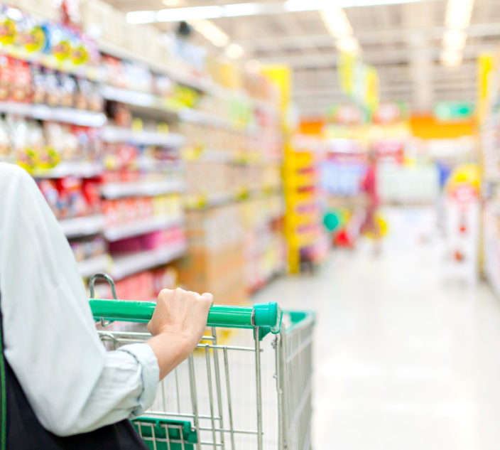 Woman pushing a shopping cart in the supermarket, focus on woman