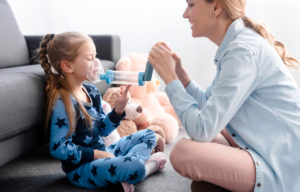 Happy mother holding inhaler with spacer for child.