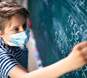 Little boy wearing face mask doing math calculations.