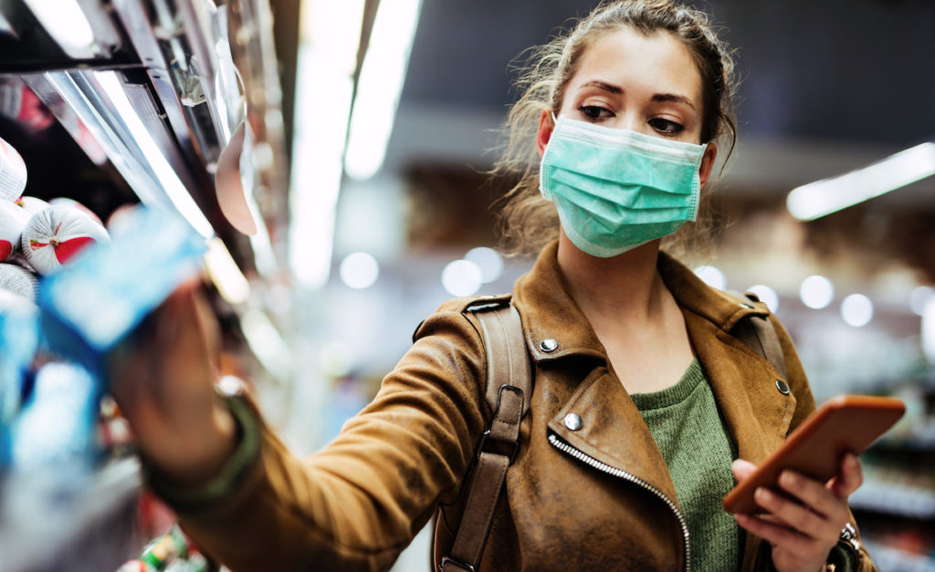 Young woman with face mask using mobile phone and buying groceries in the supermarket during virus pandemic. (Young woman with face mask using mobile phone and buying groceries in the supermarket.
