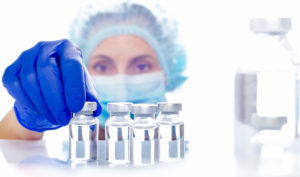Female nurse in safety mask and gloves takes vial with liquid medicine from refrigerator shelf
