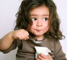 Little girl eating soy yogurt to avoid her eoe trigger.