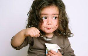 Little girl eating soy yogurt to avoid her eoe trigger.