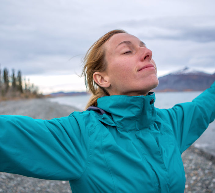 Young cheerful woman by the lake enjoying nature. Arms outstretched for positive emotion.