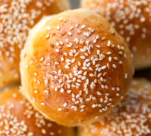 five hamburger buns with sesame seeds