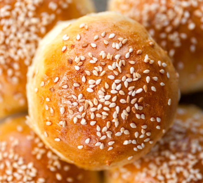 five hamburger buns with sesame seeds