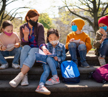 A teacher with small children sitting outdoors in city park, learning group education and coronavirus concept. (A teacher with small children sitting outdoors in city park.