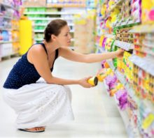 Woman at grocery store reading label.